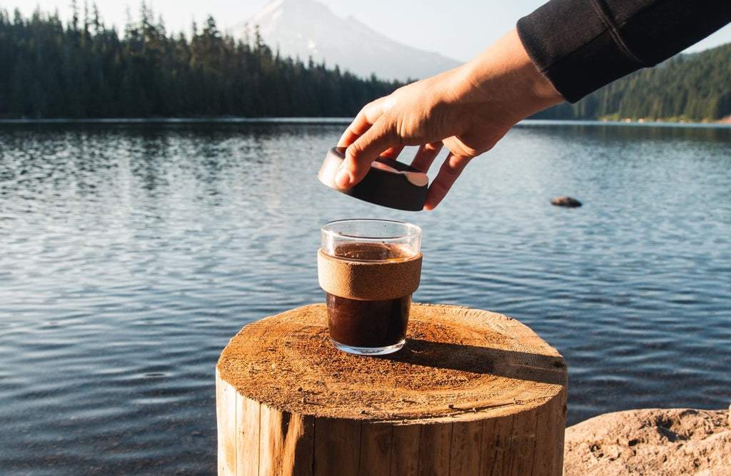 Glass KeepCup coffee travel mug resting on a stump in front of a picturesque lake bordered by foliage and trees