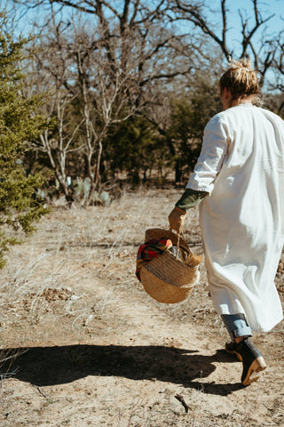 Miranda walks through a paddock with a basket full of cochineal