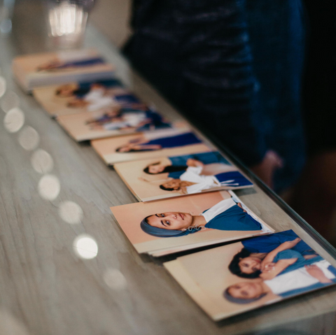 Portraits of Asian-American womxn printed on customers lay on a counter for guests of the event to take with them