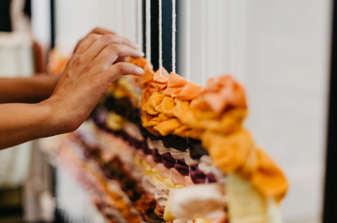 a hand weaving a large scrap of naturally dyed fabric from the Miranda Bennett Studio collection on a community loom created for the Sunday Social at the MBS Flagship