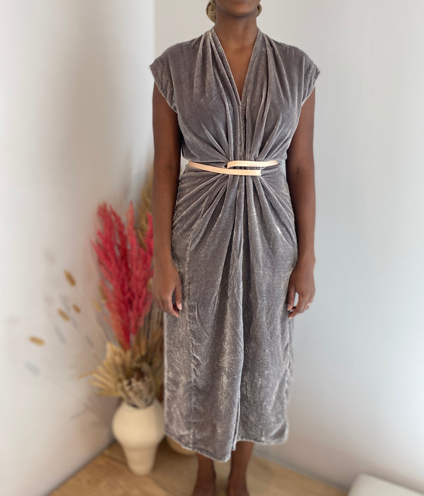 Model stands facing the camera in a silver grey velvet dress with short sleeves that hits between her knee and ankle. The dress is gathered at the waist with a leather belt creating pleated drapes of fabric.