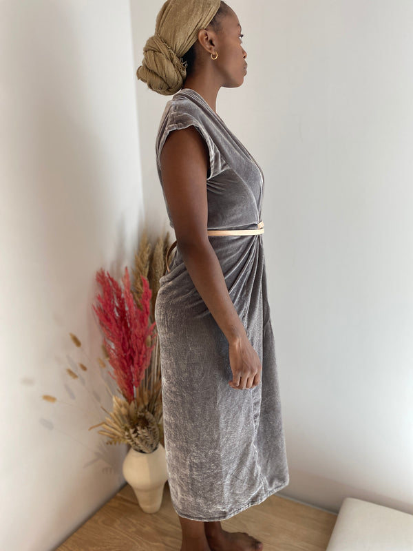 Model stands facing the side in a silver grey Velvet dress with short sleeves. The dress is gathered at the waist with a leather belt creating pleated drapes of fabric.