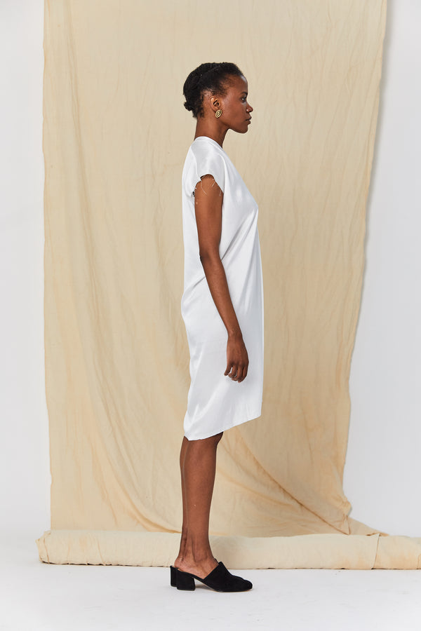 The model is facing perpendicular to the camera. The drape of the silk charmeuse dress shows it hits right on the knee in the front and right below the knee in the back.