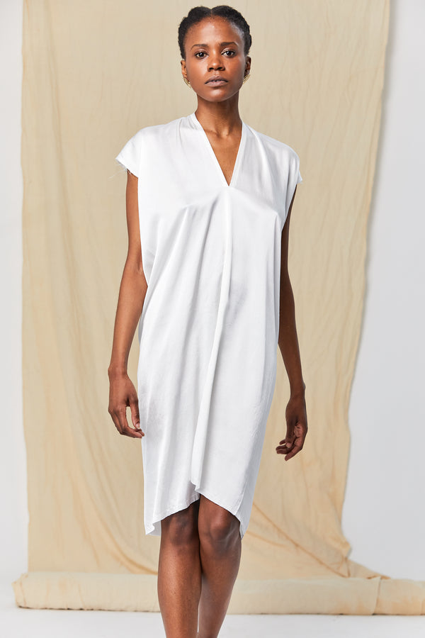 The model stands facing the camera in a White, V-Neck Dress with Short Sleeves. The dress falls just below the knee. The drape of the fabric is soft and buoyant.