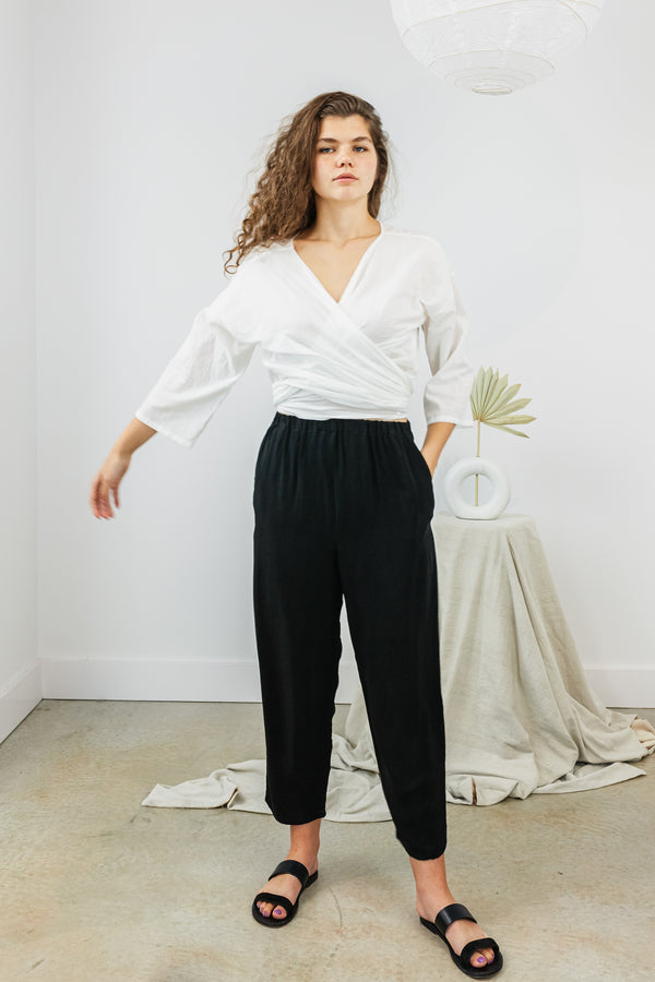 A model stands with the MBS White Cotton Dobby Shirt Worn Wrapped Across the front and tied in the back. The sleeves are 3/4 length, and the area of the shirt is generous, it could be tied in a large knot or bow in the back, or wrapped around an additional time and wrapped in the front. The model wears a knot tied at her back. The fabric has a textured finish that is subtle. The fabric is evocative of men's shirting.