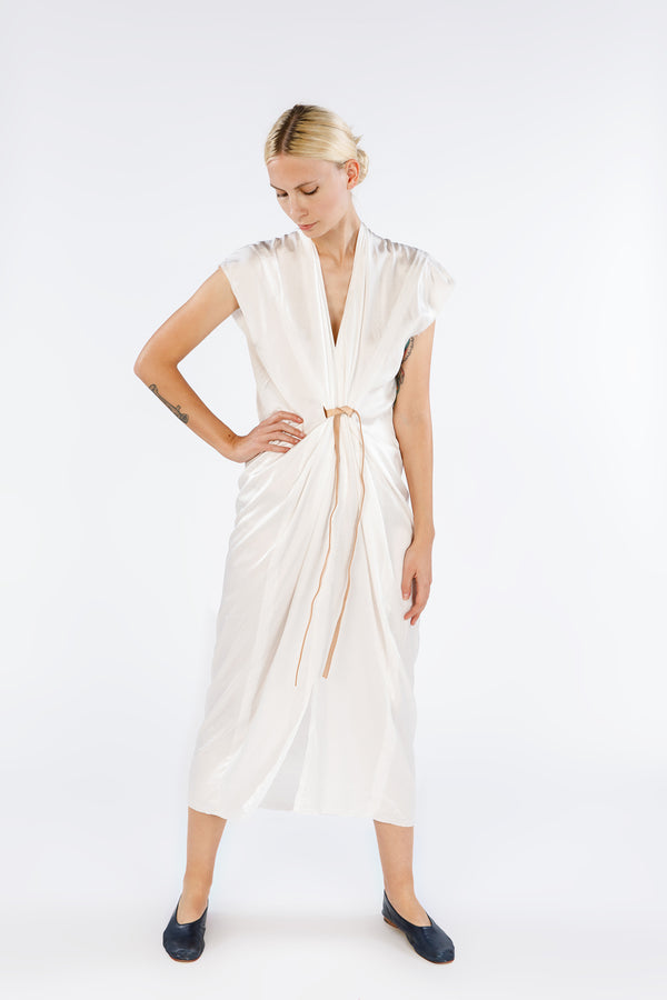 Model is standing directly in front of the camera in an off-white v-neck short sleeve dress with a leather belt. The belt causes a nice drape effect that starts at the waist.