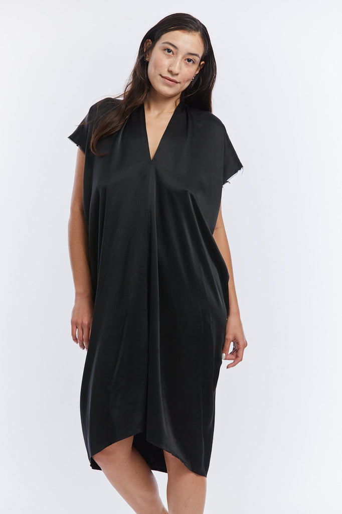 Black silk charmeuse dress with v-neck and short sleeves that drapes over her body and hits at her knee.