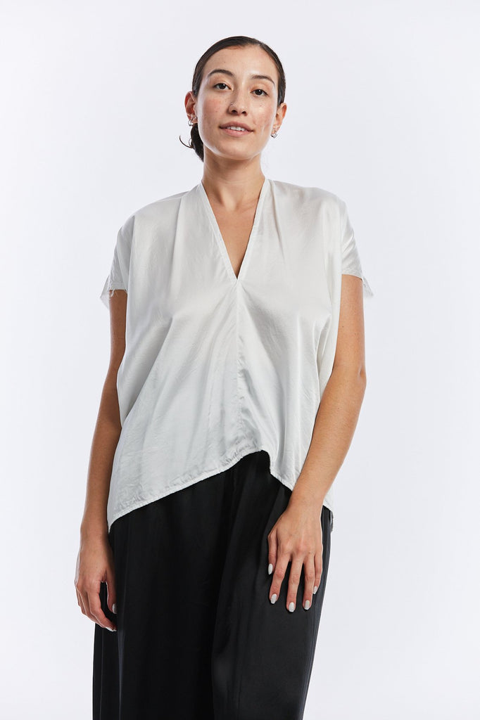 The model is standing face forward in a v-neck short sleeve silk charmeuse top. The shirt is white and has a boxy cut that drapes lightly.