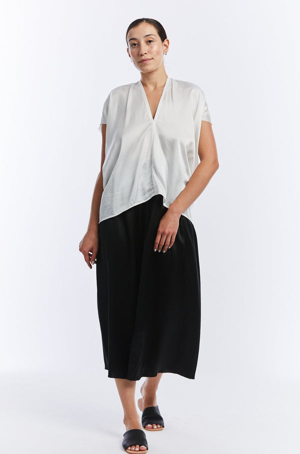Model is standing face forward in a white v-neck short sleeve silk charmeuse top. The top drapes lightly right up the hip.