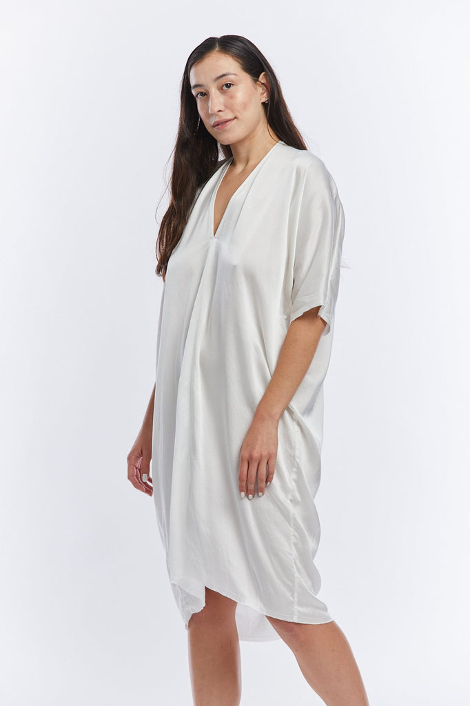 The model is standing at an angle toward the camera. She is wearing a short sleeve silk charmeuse dress with a v-neck in white. The drape of the fabric is super light and soft.