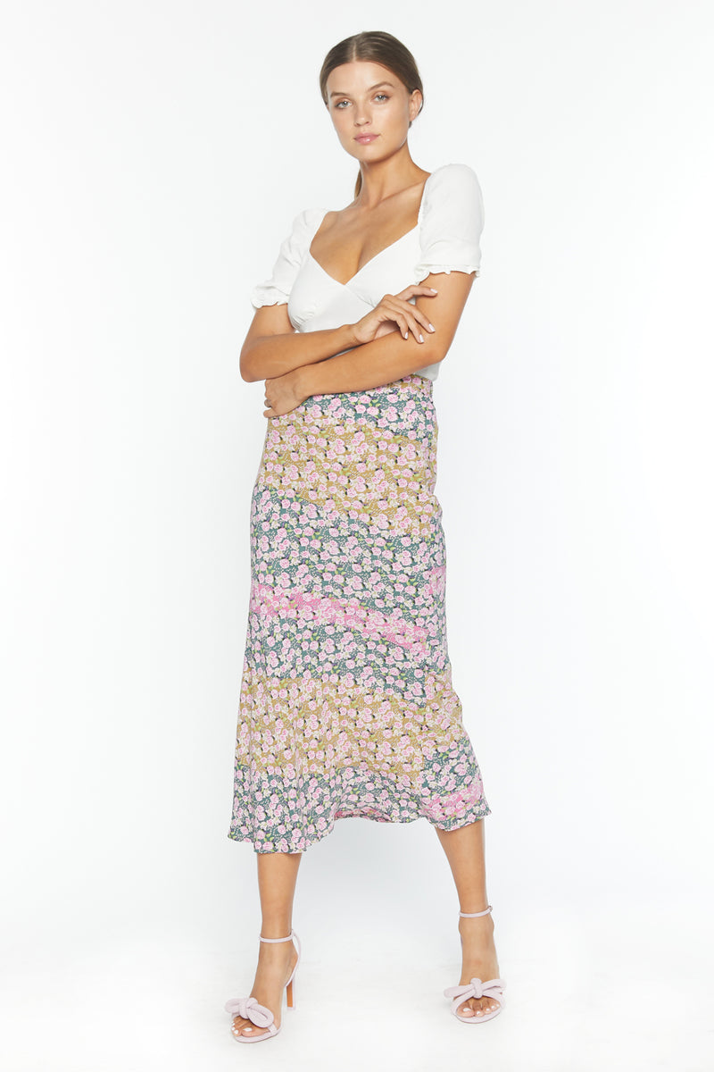 Model in long form fitting floral patterned skirt