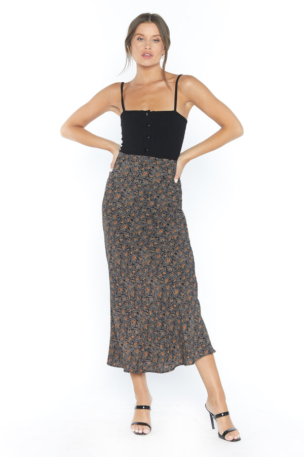 Model in long form fitting brown patterned skirt