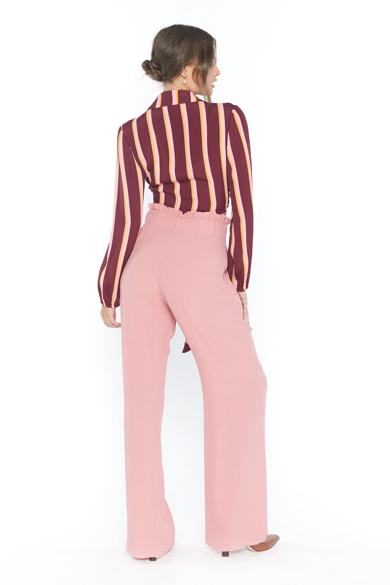 Model wearing pink high waisted pants with ruffle waistband