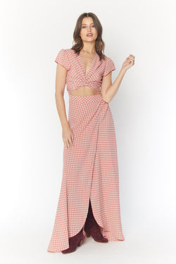 Model in pink polka dot floor length maxi dress with wrap top and leg slit