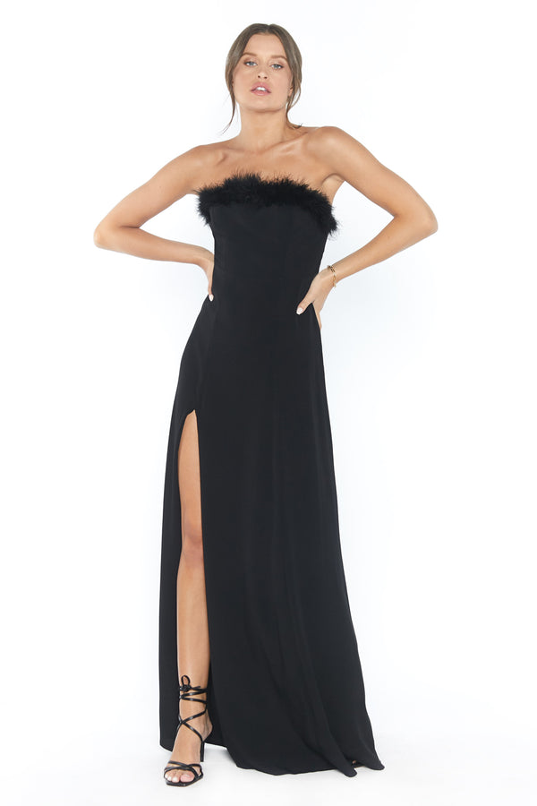 Model wearing black maxi dress with leg slit and feather trim