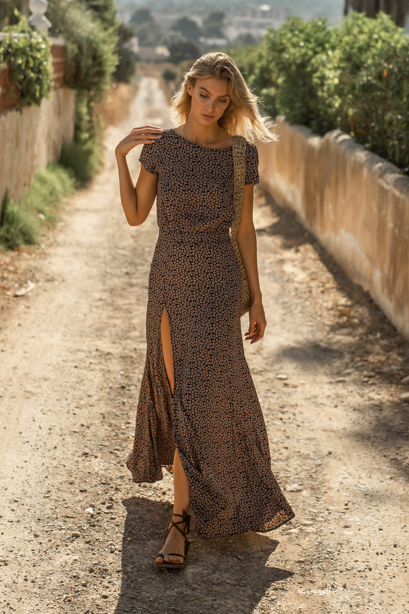 Model wearing maxi dress with short sleeves and leg slit