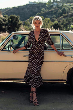 Model wearing brown polka dot maxi dress with 3/4 length sleeves