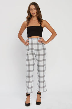Model wearing white checkered cropped pants