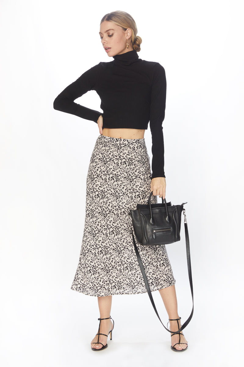 Model wearing form fitting leopard print skirt