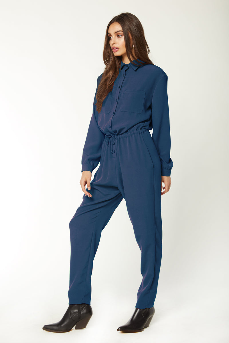 Model wearing navy blue long sleeve jumpsuit