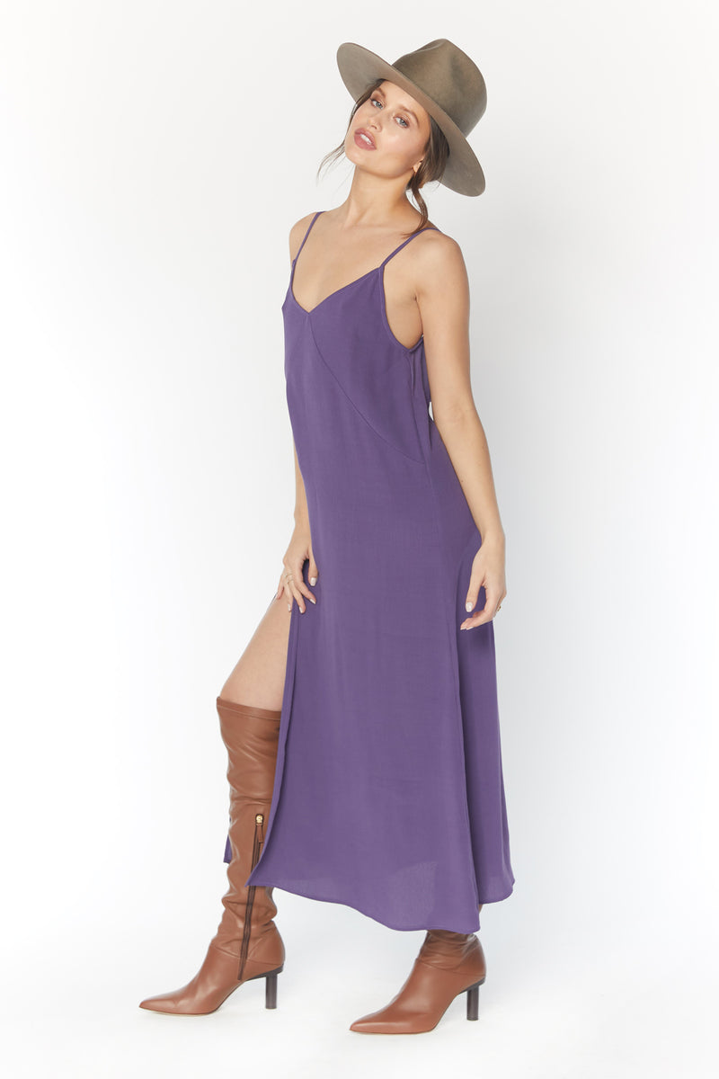 Model wearing purple midi dress with leg slit