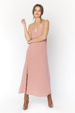 Model wearing pink polka dot midi dress with leg slit