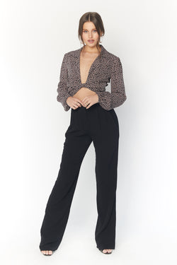 Model wearing black high waisted pants with ruffle waistband