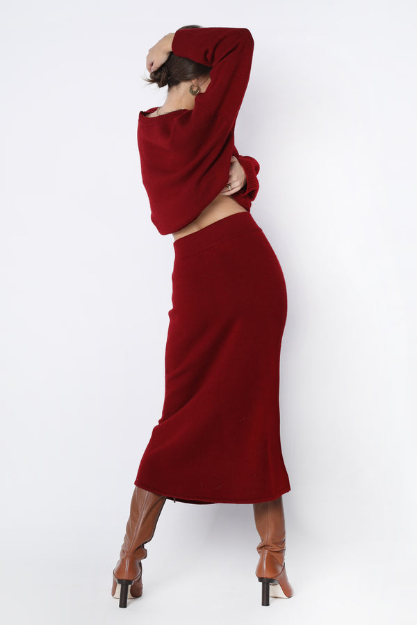 Model wearing red form fitting knit skirt