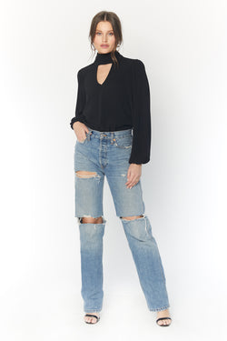 Model wearing black long sleeve blouse with keyhole cutout