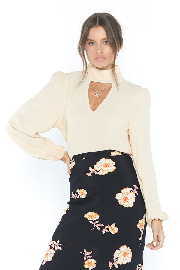 Model wearing cream colored long sleeve blouse with keyhole cutout