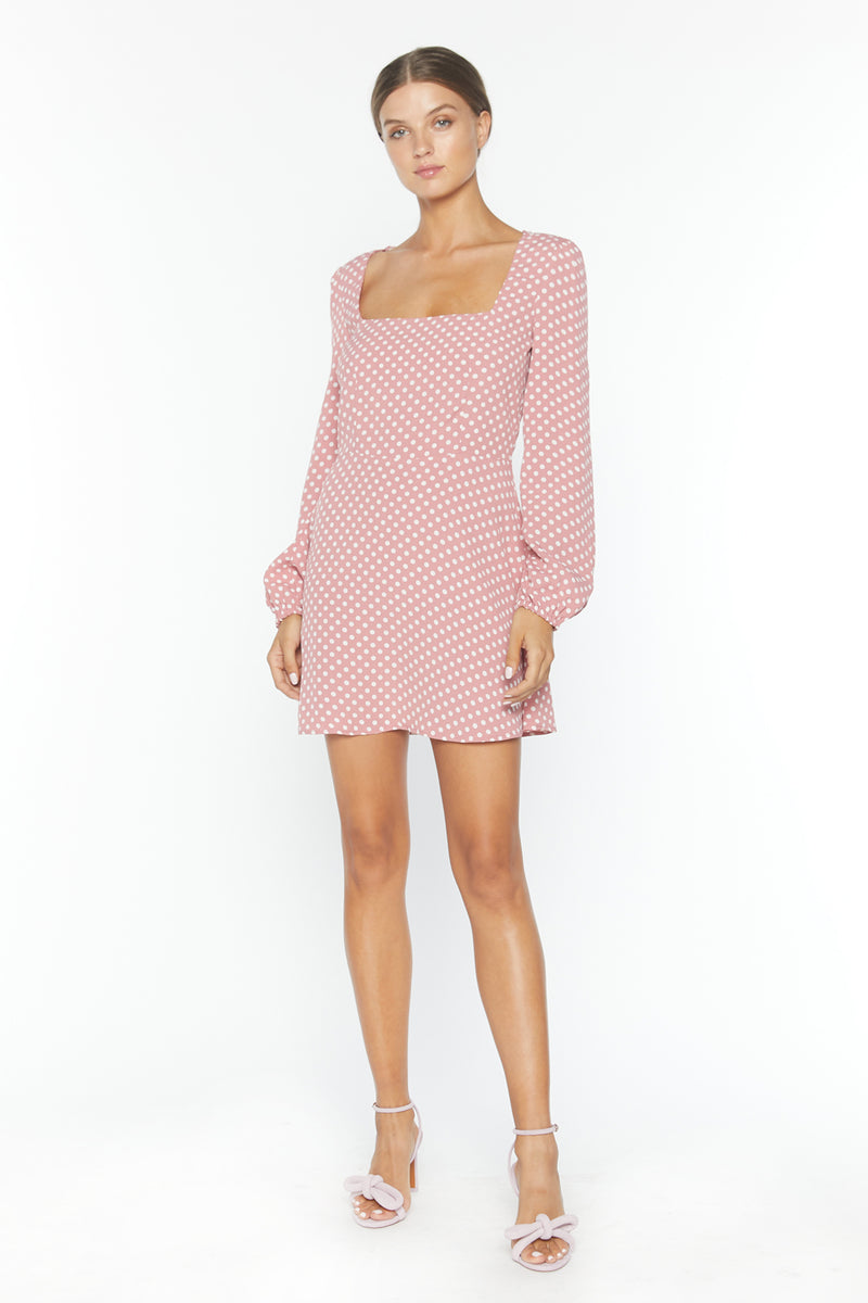 Model wearing pink polka dot long sleeve mini dress