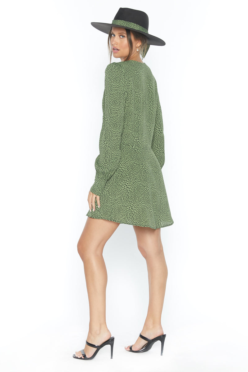 Model wearing green long sleeve mini dress