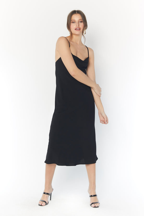 Model wearing black midi dress with thin criss-cross straps