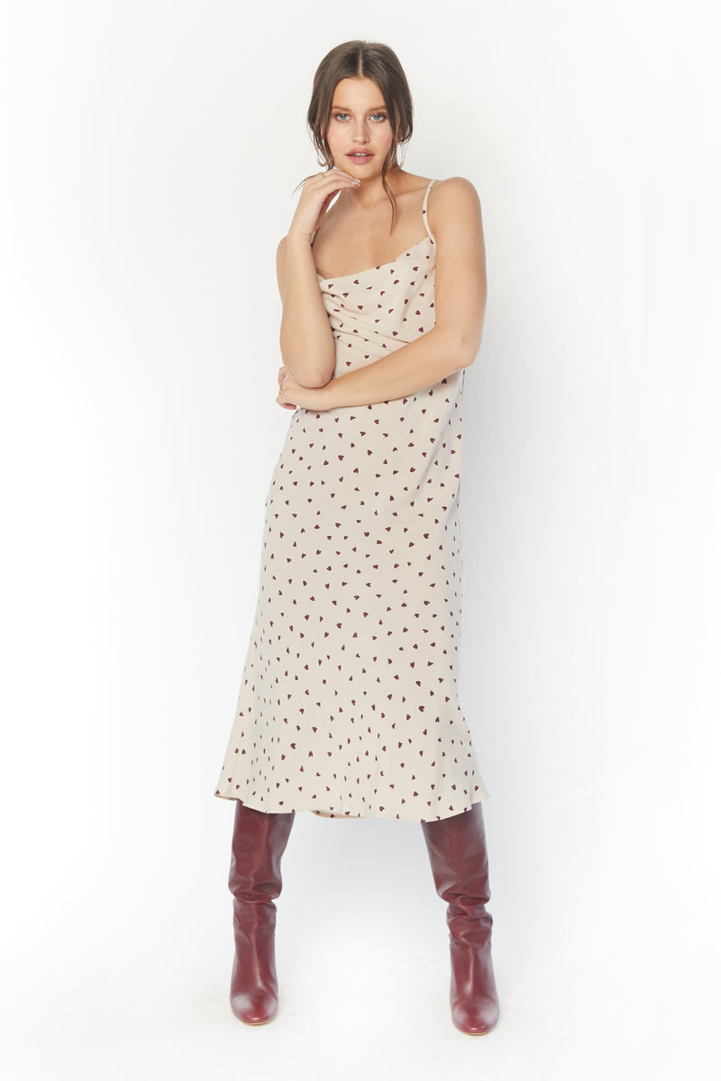 Model wearing heart print midi dress with thin criss-cross straps
