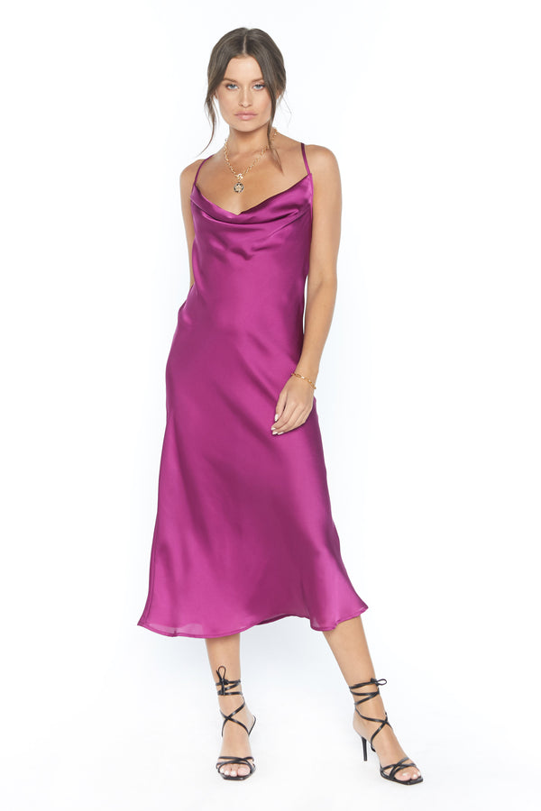 Model wearing ruby satin midi dress with thin criss-cross straps
