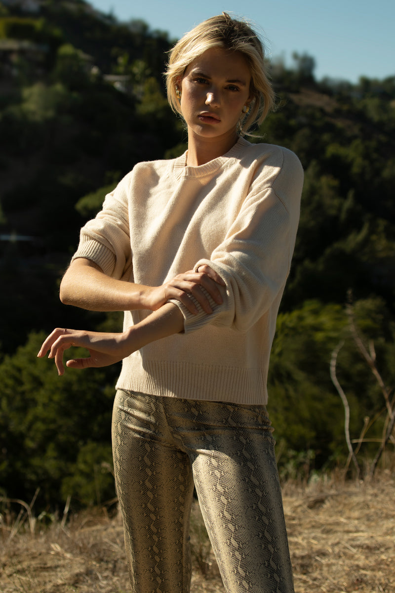 Model wearing cream colored long sleeve sweater