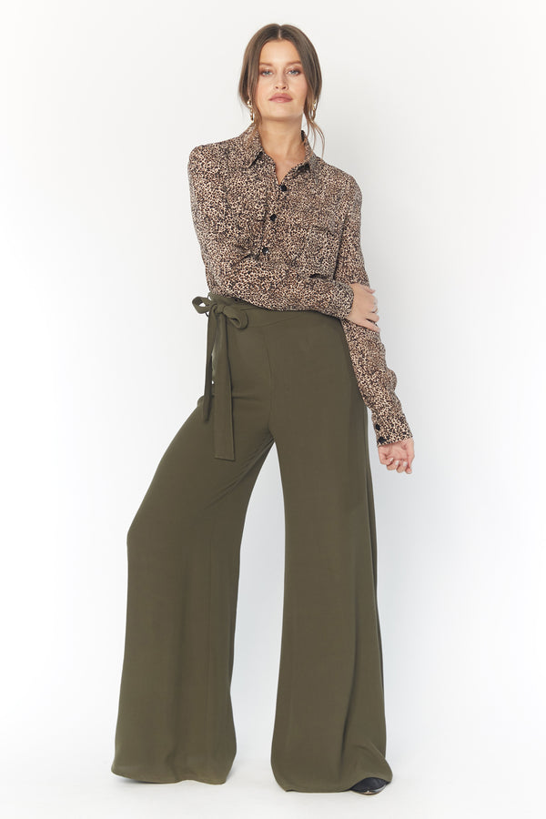 Model wearing green wide leg pants with fabric belt