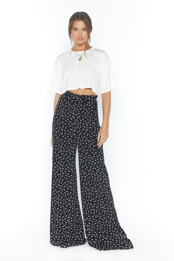 Model wearing black wide leg printed pants with fabric belt