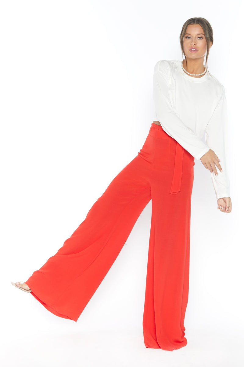 Model wearing red wide leg pants with fabric belt