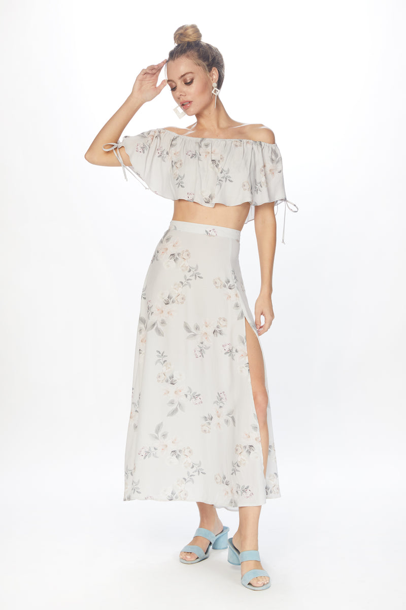 Model wearing grey floral printed skirt with leg slit