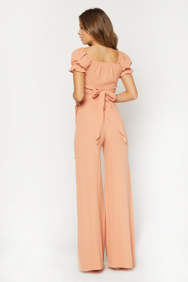 Model in peach colored short sleeve wrap top