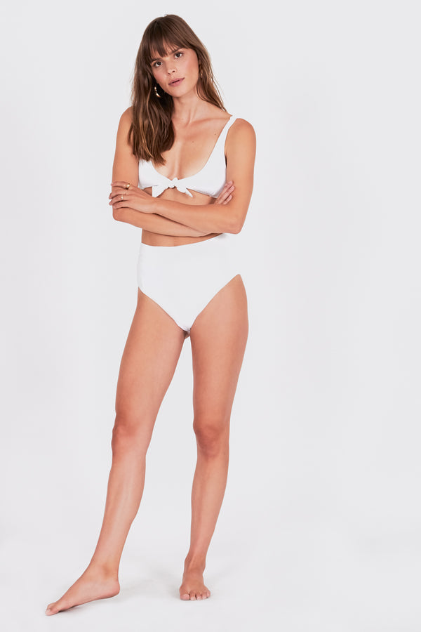 Model in high waisted white swim suit bottoms