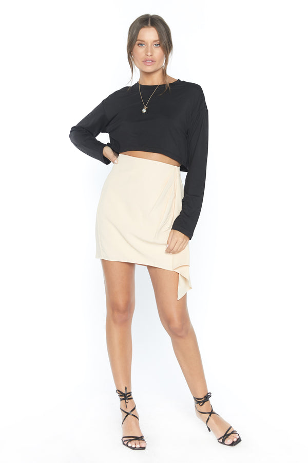 Model wearing cream colored mini skirt with ruffle