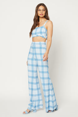 Model in blue checker-patterned crop top with adjustable straps