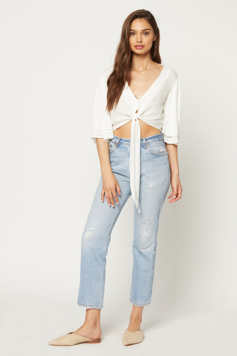Model wearing white v-neck cropped blouse