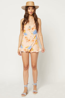 Model wearing peach colored romper with floral print
