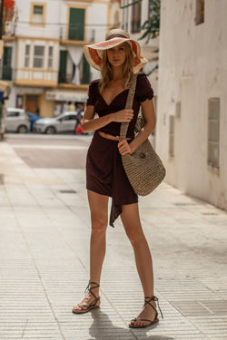 Model wearing plum mini skirt with ruffle