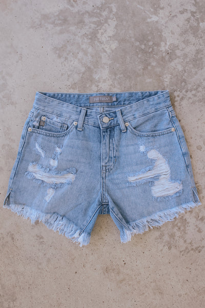 Women's light wash distressed cut off jeans.