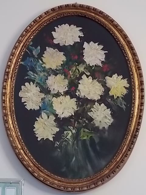 Oil painting on board of flowers in an oval frame