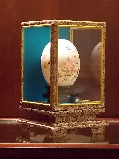 Hand-painted egg with a floral design on a stand in display case